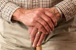 This shows an old man's hands holding a walking stick