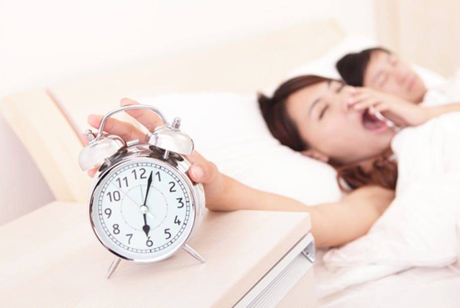 This shows a sleepy woman reaching for an alarm clock