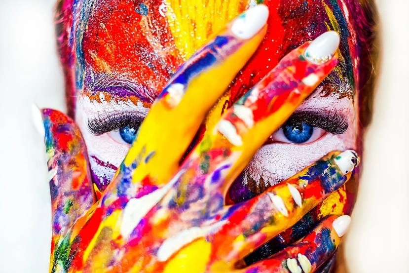 This shows a woman with her face painted multiple colors