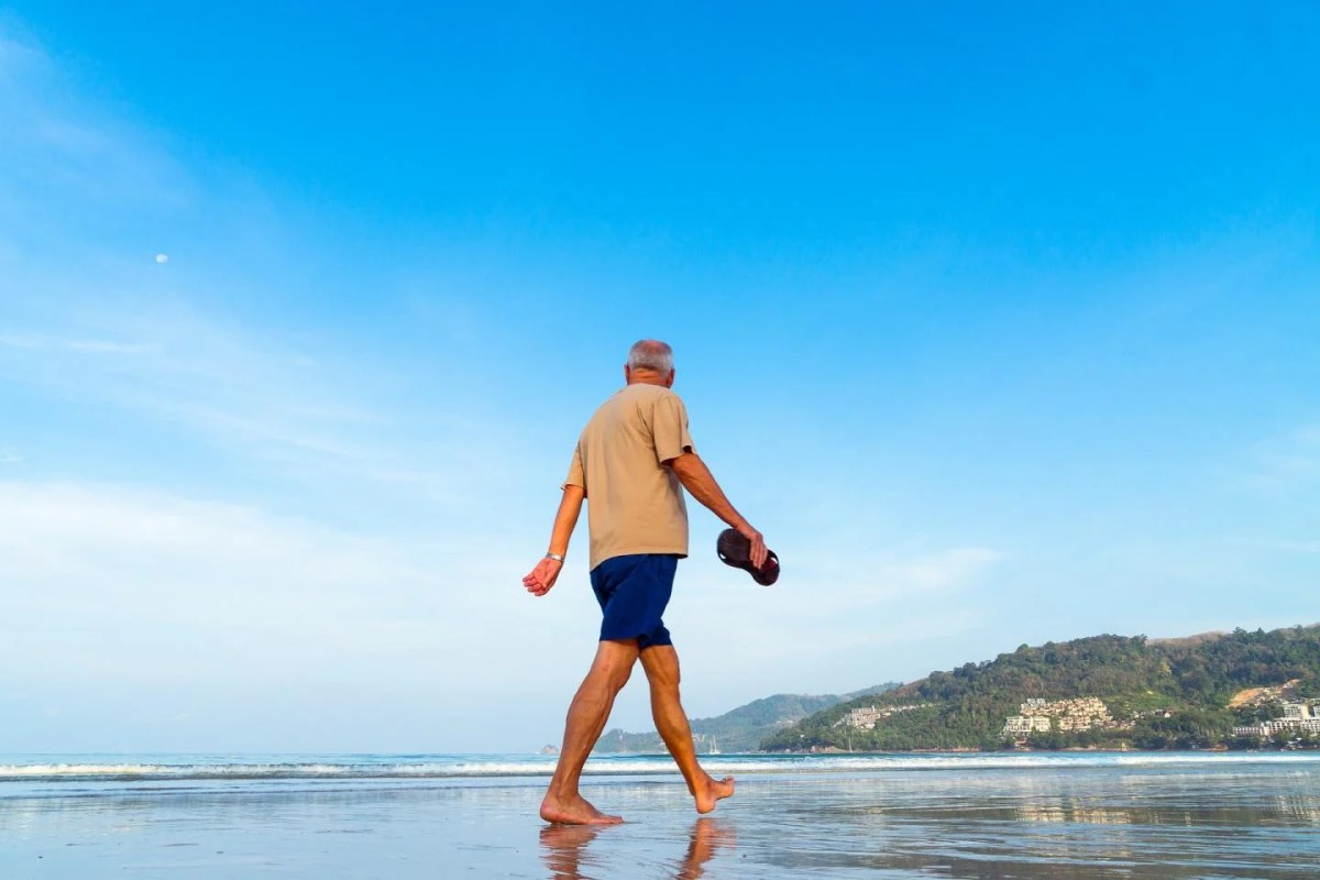 This shows an older man walking on a beach