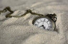 This shows a pocket watch in the sand