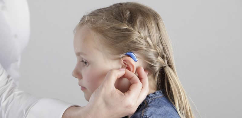 This shows a little girl with a hearing aid