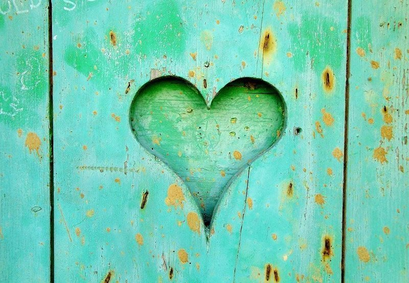 This shows a heart carved into a green wooden door