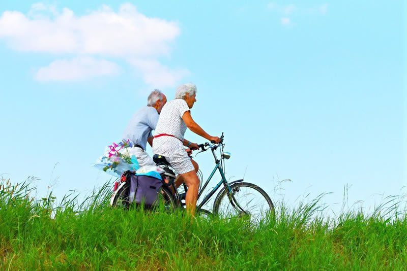 This shows an older couple riding bicycles