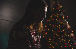 This shows a depressed looking woman sitting by a christmas tree