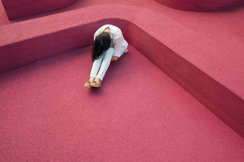 This shows a sad woman sitting on a pink rug