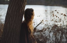 This shows a girl standing alone by a tree and looking at a lake
