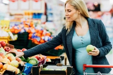 This shows a pregnant woman buying apples
