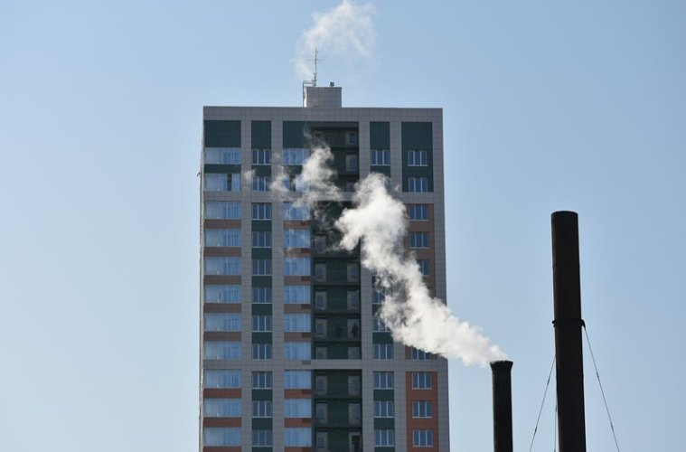 This shows an apartment building next to a smoke stack