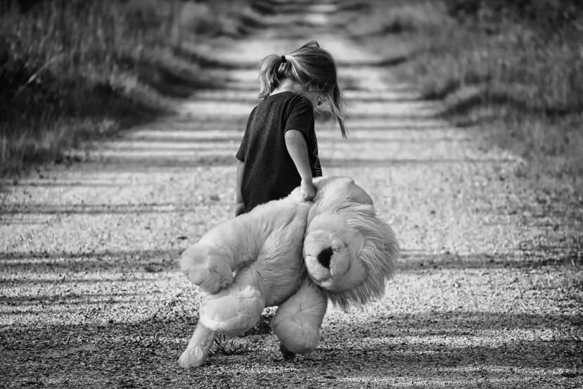 This shows a child with a teddy bear