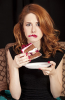 Redhead girl secretly eating cake.