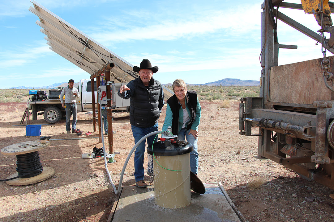 Image: Greg Newby (l) and Teri Knight celebrate the installation of a new solar pumping plant.