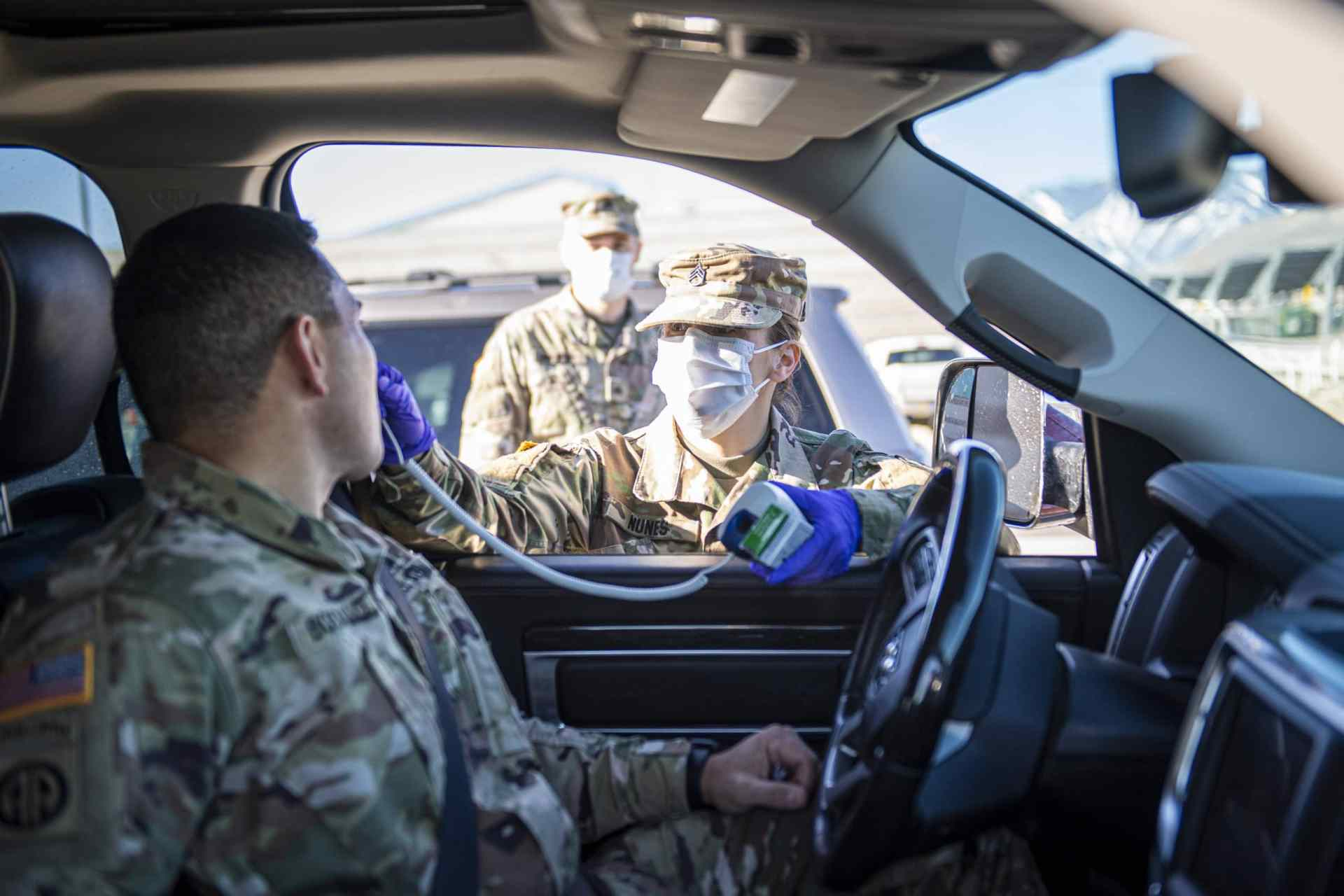 Staff Sgt. Jennifer Nunes, a health care specialist assigned to the Northern Nevada Medical Detachment Nevada National Guard, checks the temperature of a Soldier at the front gate of the Office of the Adjutant General complex in Carson City, April 1, 2020. The Nevada National Guard started screening the Soldiers, Airmen, and civilians that continue to work despite the COVID-19 outbreak. (National Guard photo by Sgt. Walter H. Lowell)