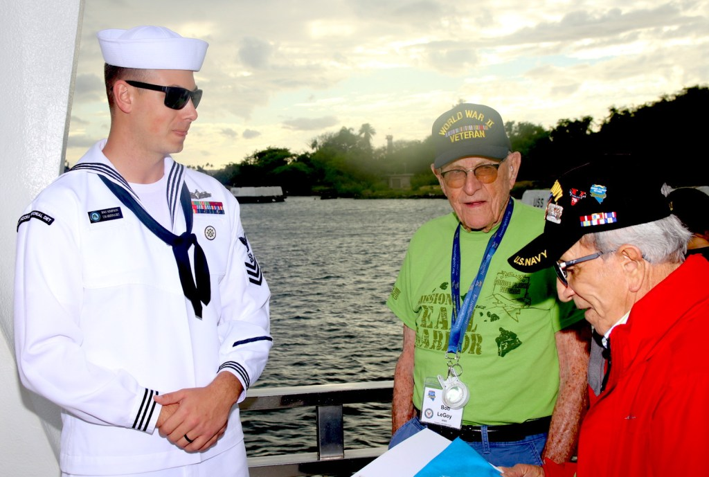 Robert LeGoy, center, and Gol Sanchez, right, both World War II Navy veterans, talk to a sailor at Pearl Harbor. Steve Ranson / NNG