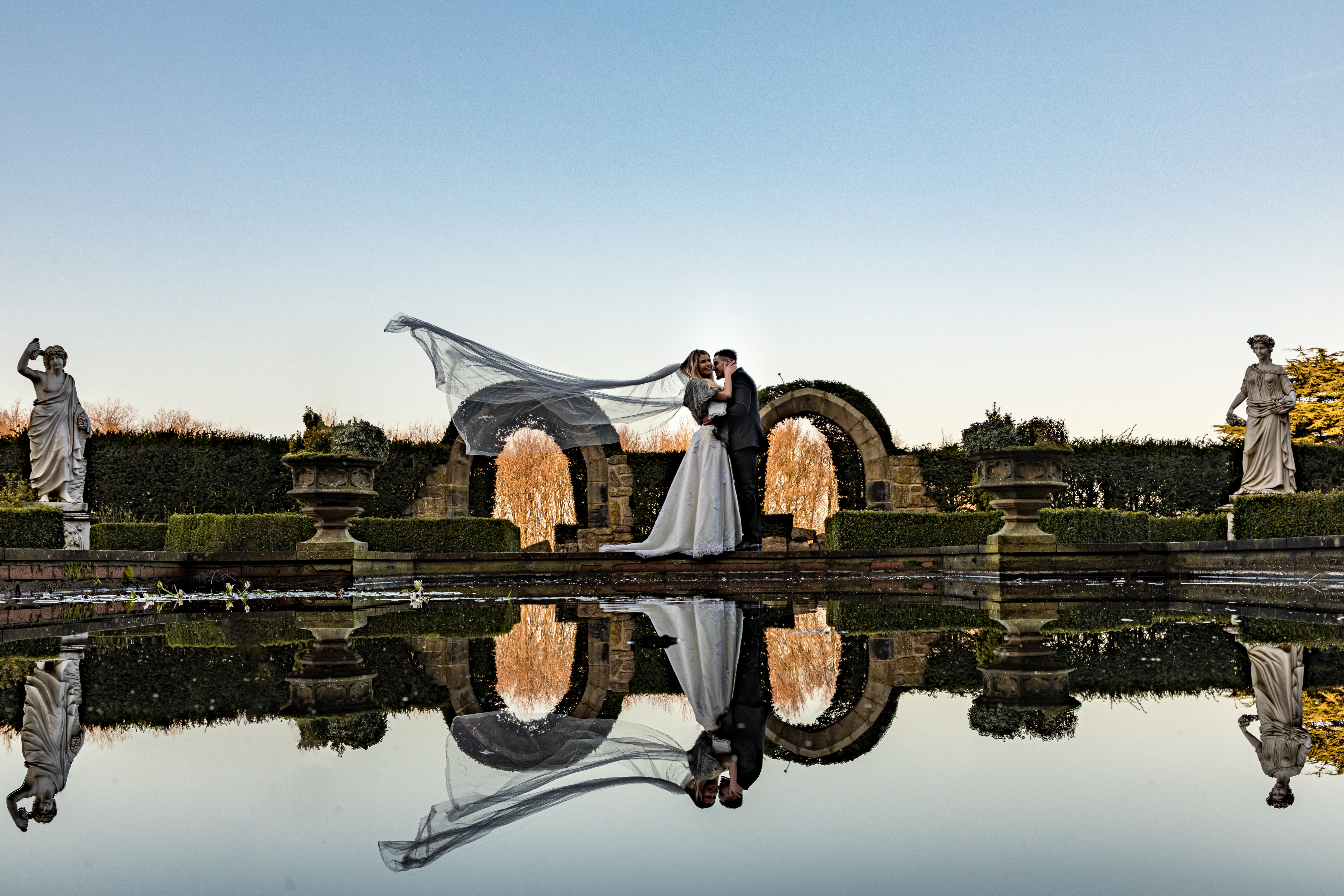 Bride and Groom next to ornamental pond. Embracing and veil moving in wind.