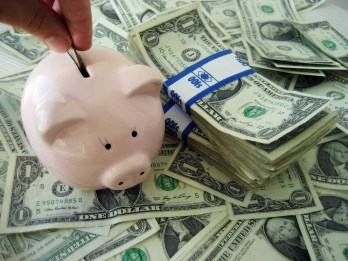 Depositing money in a piggy bank | neveralonemom.com