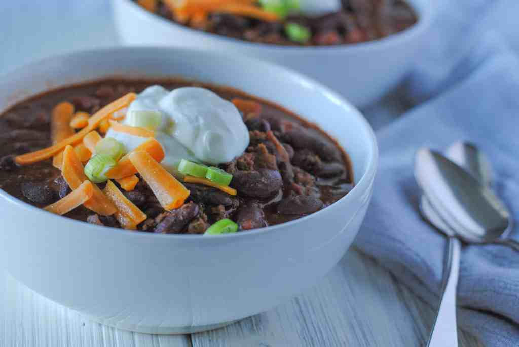 chili in bowls with sour cream and cheese and green onion