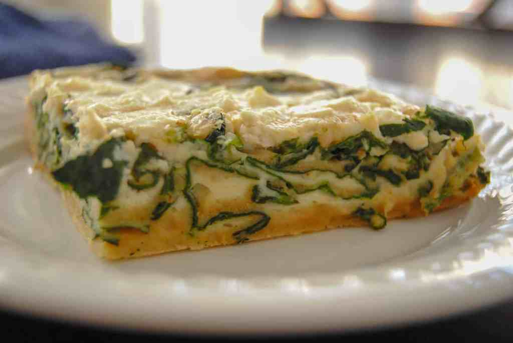 side view of cut spinach and feta quiche