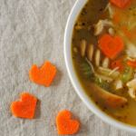 heart shaped carrots and a bowl of chicken soup