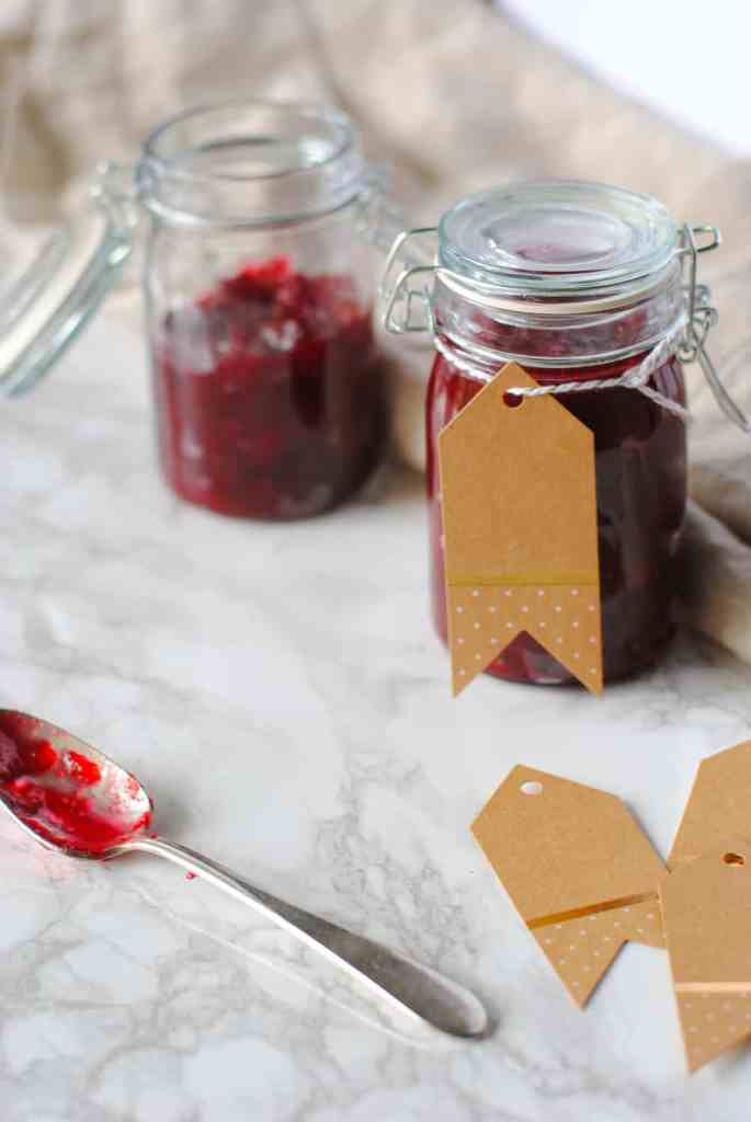 Small jars of spiced cranberry sauce with gift tags