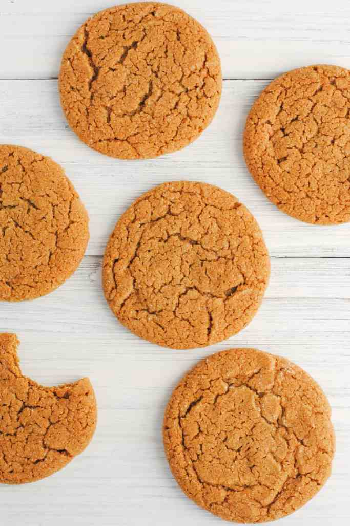 ginger cookies on white background, one with a bite taken