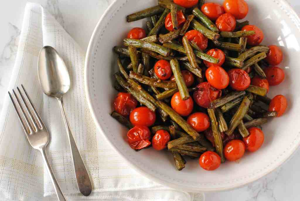 balsamic green beans and tomatoes in serving dish with fork and spoon