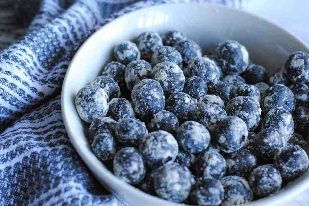 blueberries dusted with flour in white bowl