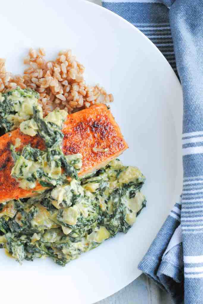 creamy sauce of spinach and artichokes over salmon and farro on a white plate