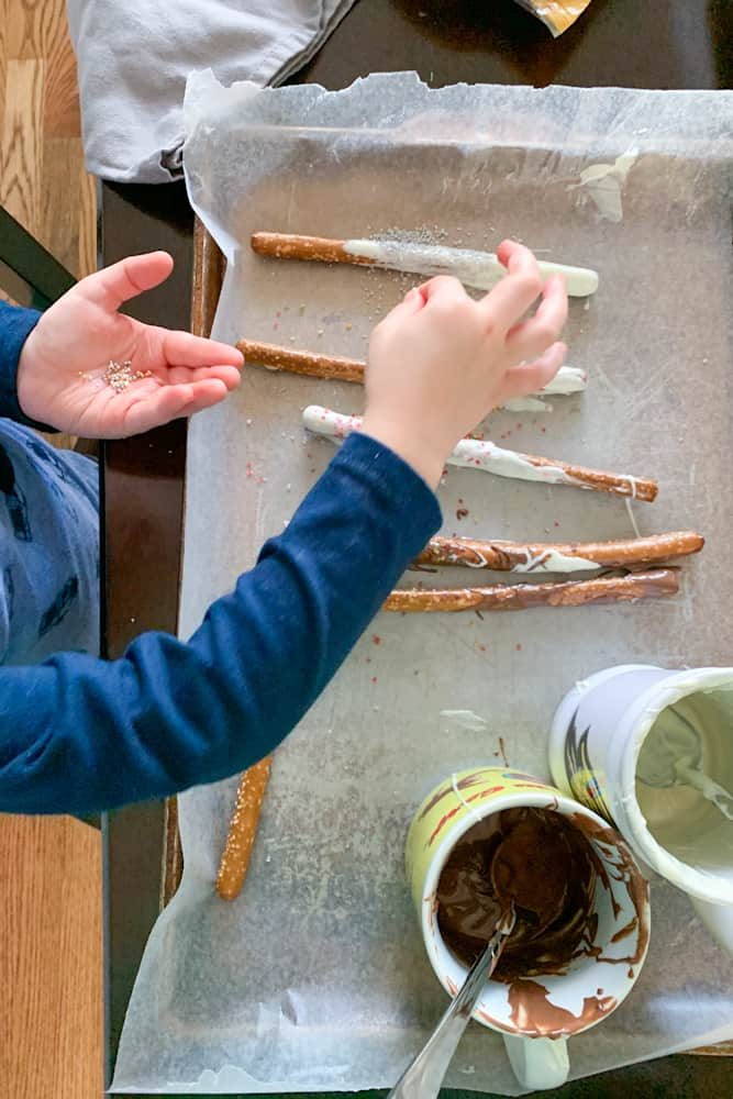 child's hands topping chocolate dipped pretzels with sprinkles