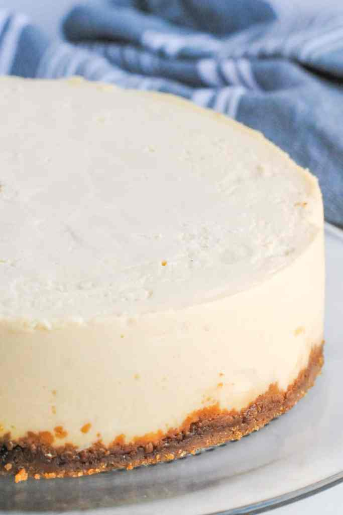 cheesecake on a white plate with gray and white striped towel in background