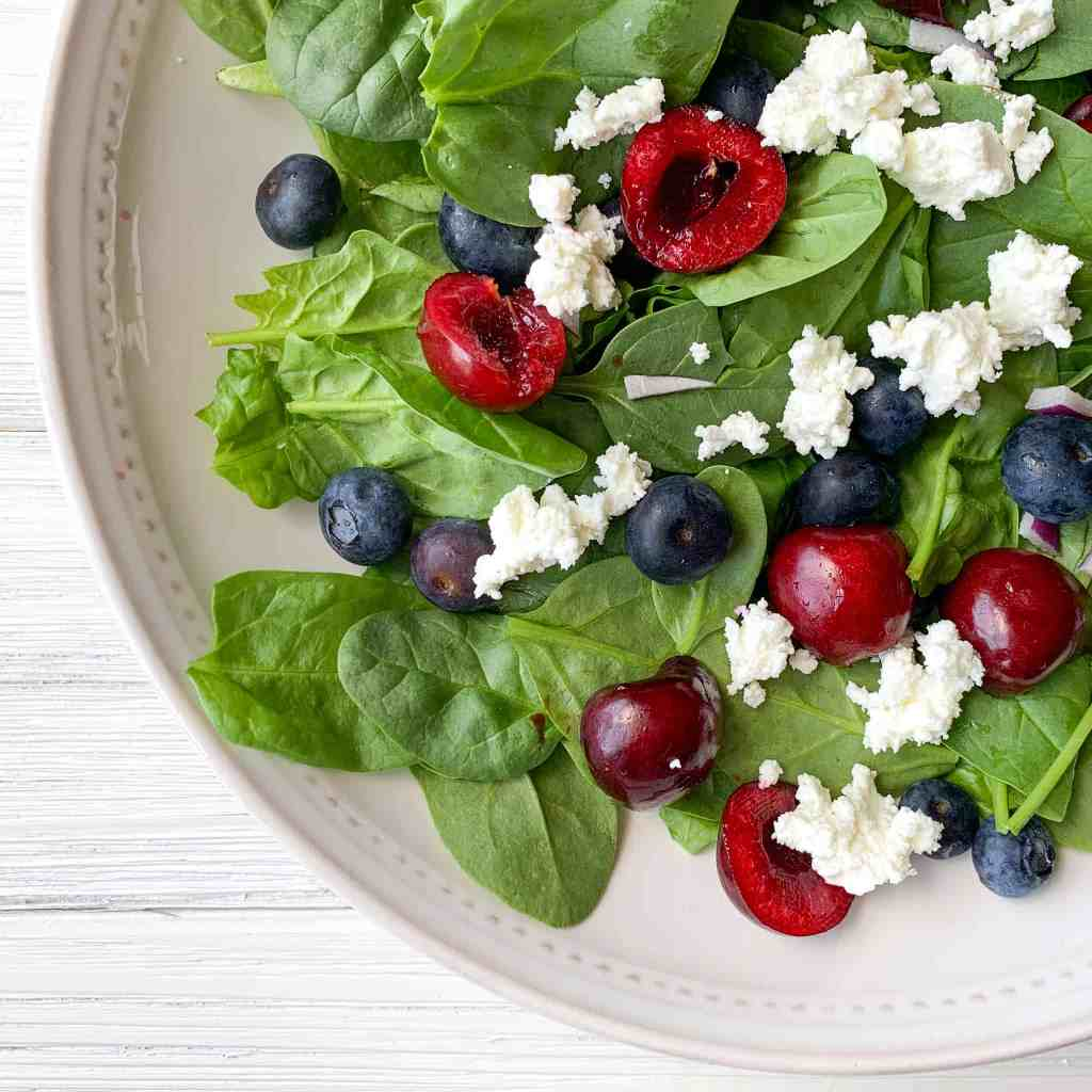 white bowl filled with spinach salad, and topped with cherries, blueberries, goat cheese, and red onion