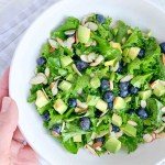 hand holding a white bowl with kale salad topped with blueberries, avocado, sliced almonds and honey lime vinaigrette dressing