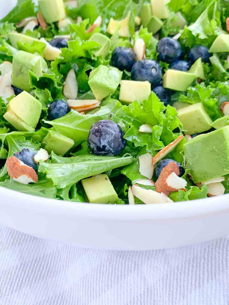 close up of white bowl with kale salad topped with blueberries, avocado, sliced almonds and honey lime vinaigrette dressing