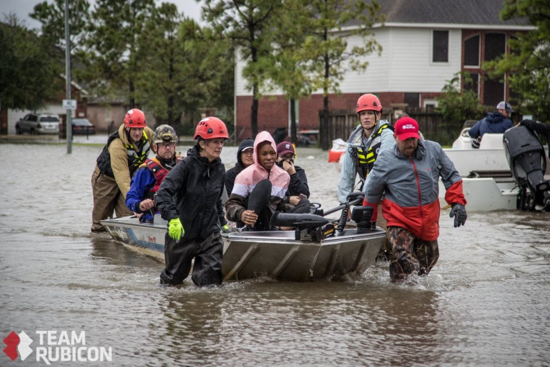 Team Rubicon volunteers rescue Houston residents from flood waters in a small boat.