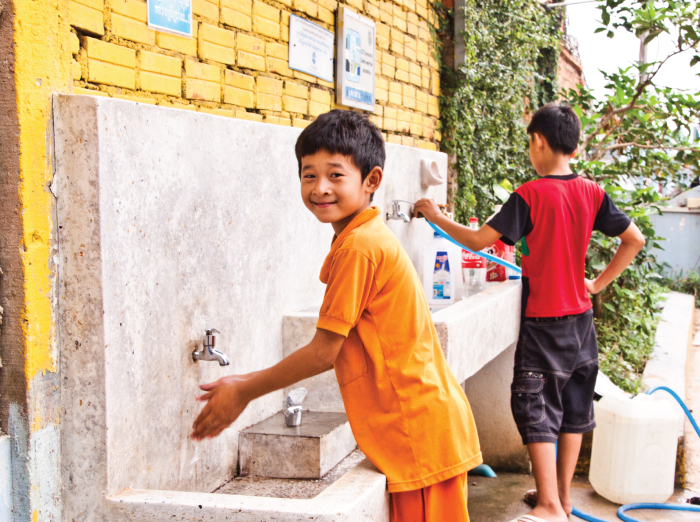 Boy washes his hands at water station
