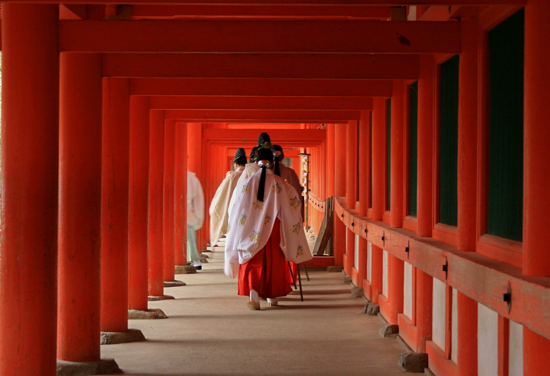 Monks walking through a red-pained hallway