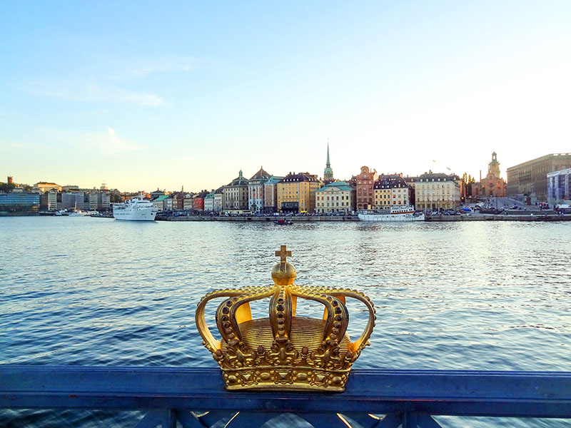 a crown on a bridge by a harbor - top 10 places in sweden