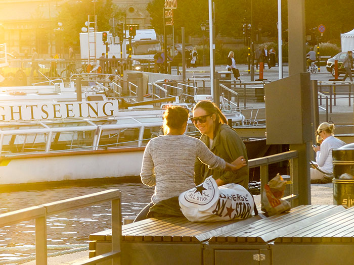 two women seated along a harbor - top 10 places in sweden