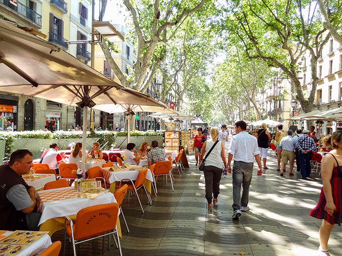 a couple walking past places to eat in Bracelona