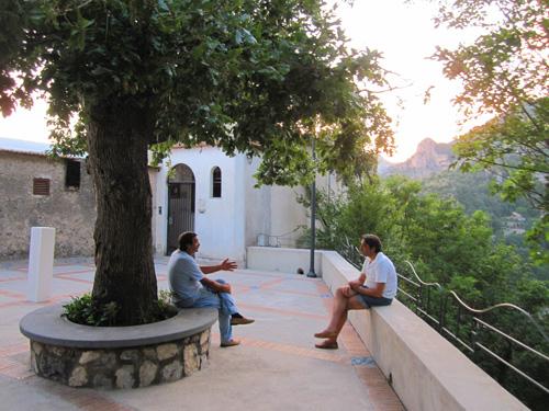 two men sitting a talking under a tree in an Amalfi Coast town