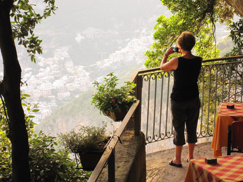 a woman taking a photo from a terrace in Nocelle