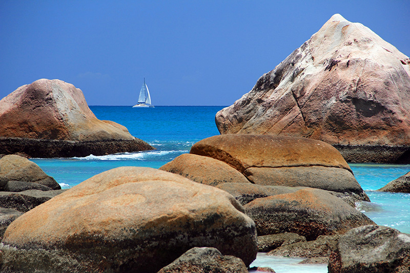 large rocks and a sailboat