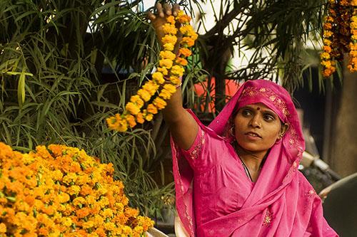 Woman holding flowers during Diwali - New Delhi travel tips