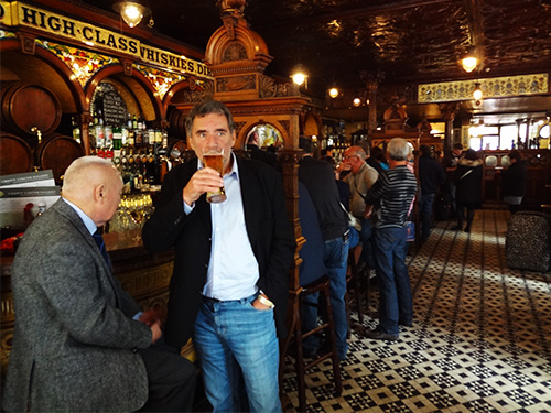 man sipping a pint of beer in a bar