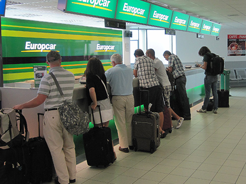 people at an airport car rental counter