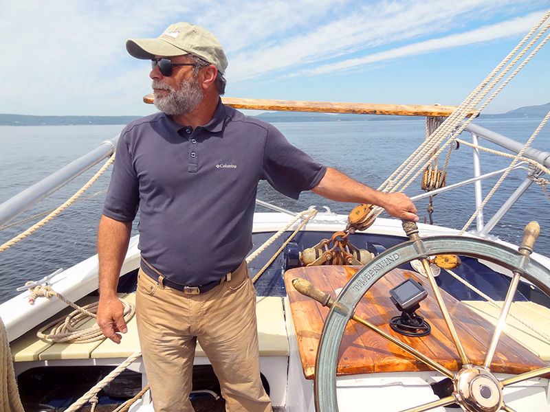 A Captain at the helm of one of the windjammers in maine