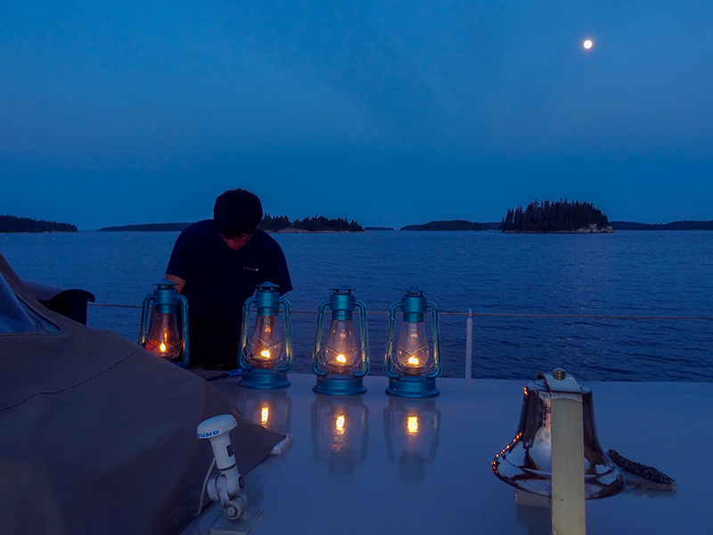 Lighting the lanterns for the night on the deck on windjammers in Maine
