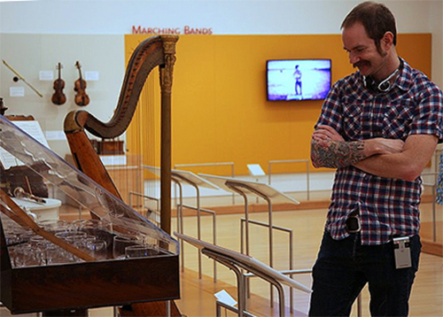 man at a music instruments exhibit