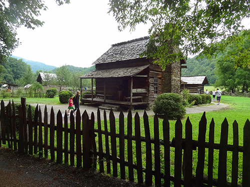 people by a log cabin seen on a Smoky Mountains road trip