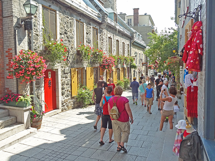 people walking along a street with old houses on a tour of Quebec City